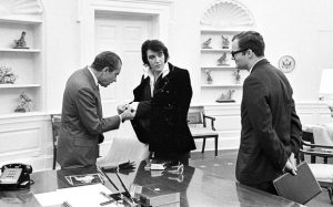 Nixon gets a close look at Elvis's get-up, watched by White House aide Egil Krogh. Photograph: Getty Images